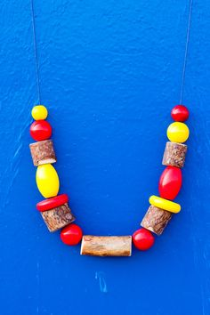 This unique wooden bead necklace is part of the limited ethnic necklace series and consists of raw wooden discs as well as painted vintage geometric