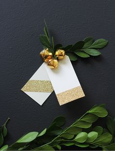 Glitter gift tags with gold bells and a bit of greenery.