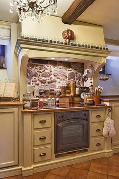 Kuchyň je nádherná i praktická: při vaření je vše při ruce. Kořenky mají své místo na krbové římse, dózy, lahvičky s dochucovadly, vařečky jsou kolem varné desky.