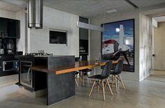 une cuisine avec des murs en béton et aux accents noirs