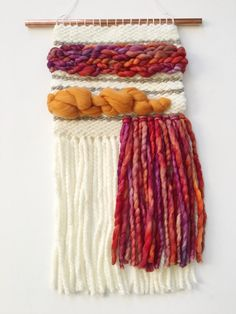 Handwoven one-of-a-kind wall hanging. Created with care and patience on a homemade lap loom. Made with mixed fibers in cotton, wool and hand-dyed wool roving. Hangs on a copper pipe. Makes the perfect whimsical and unique addition to any room! Approximate Dimensions: 8 x 17