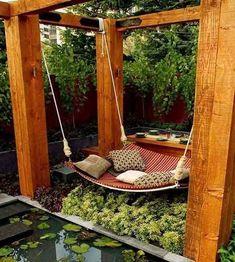 Pergola doe het zelf voorbeeld, degelijke structuur van dikke balken waaraan een hangmat is opgehangen. Romantisch plekje in de tuin.