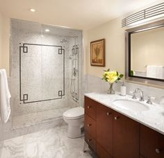 White marble bathroom with black accent tile and cherry wood cabinets - LUX Design