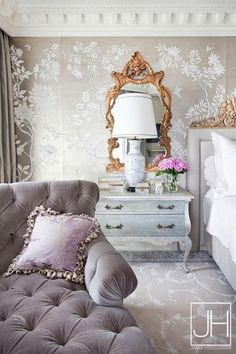 Gray and gold French bedroom features a wall clad in gold metallic wallpaper lined with a gray bed accented with gold trim next to a gray French nightstand under gold ornate mirror.