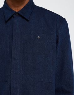 From Études, an overshirt in Indigo. Pointed collar. Concealed full snap button front placket. Two large chest pockets with snap button closures. Straight back yoke. Snap button cuffs. Straight hem with side splits.   • 100% cotton • Machine wash warm,