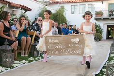 """Two adorable flower girls donned ivory dresses with light pink cowboy boots. They walked down a lace-and-burlap aisle runner holding a burlap sign that read, """"Ryan, Here Comes Your Bride."""" #flowergirls Photography: Michael Segal Photography. Read More: http://www.insideweddings.com/weddings/rustic-elegant-wedding-in-ojai-valley-california/570/"""