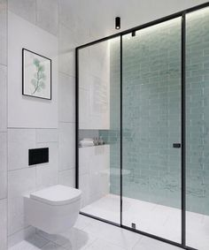 Beautiful bathroom with minimalistic decor and a glass wall to the shower cabin with a black steel frame and gorgeous green tiles on the wall.