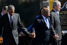 President Barack Obama, left, U.S. Rep. John Lewis, D-Ga., and Former President George W. Bush hold hands for a prayer after Obama spoke near the Edmund Pettus Bridge, Saturday, March 7, 2015, in Selma, Ala. This weekend marks the 50th anniversary of