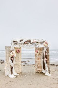 Mystical and rustic beach combination, absolutely gorgeous. Old doors, pink flowers, and draping.