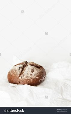 Round black bread lies on crumpled white paper on a white background. Space for text, daylight.