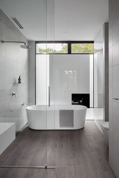 In this modern bathroom, a sliding glass door separates the shower and freestanding bath from the vanity area. #ModernBathroom #BathroomDesign