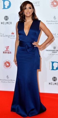Eva Longoria struck a pose on the red carpet at the Global Gift Gala in a royal blue plunging Victoria Beckham gown with a bow tied around her waist. Delicate pieces of jewelry served as the finishing touch. #celebrity #evalongoria #redcarpet