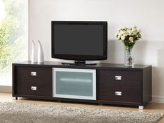 Baxton Studio Botticelli Brown TV Stand with Frosted Glass Door A Botticelli TV Stand is a sleek, modern entertainment center.Two drawers on the left end and two on the right.Drawers are perfect places to hide your electronics accessories, DVDs, and more. A sliding frosted glass door and two shelves with an adjustable-height shelf in the center. The media cabinet is made of mixed engineered woods with dark brown faux wood grain paper veneer.It finished with silver hardware and legs. Holes in…