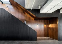 Dark walnut wood treatments line the wall and provide a contrast to the blackened wood on this staircase.