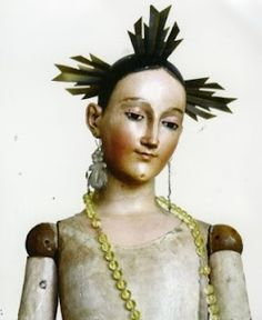 carved face of a Santos doll