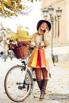 Beautiful young woman holding a bicycle and talking on phone aft - Beautiful young woman holding a bicycle and talking on phone after shopping