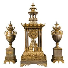 A Rare French Silvered & Gilt Bronze Chinese Pagoda Motif  Three Piece Clock Set 1860  Having an original silvered and gilt patina. The clock in the form of a pagoda with Arabic numerals over two Chinese figures one sitting playing the mandolin and the other standing with a bird on his arm. The base highly decorated with dragons and bees. The legs in a gilt bronze dragon shape.