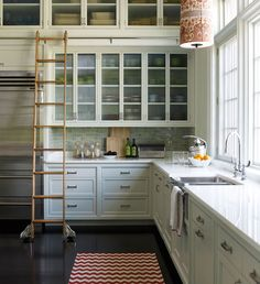 This kitchen is simply elegant! From the beautiful glass cabinetry and the gleaming white countertops to the gray and green toned brick walls, this room has a personality that is simultaneously nostalgic and innovative. From Anik Pearson Architect