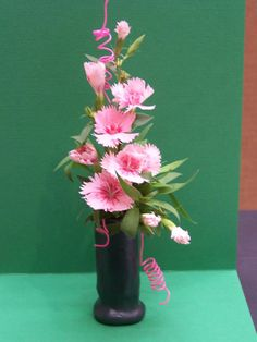 """""""Get in Line"""" at FDFGC """"Vote for Flowers"""" show. Pink dianthus, pink wire. 8"""" design, blue ribbon. Container made from Sculpey Clay. By Jan Krass"""