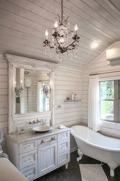 This tiny house has a clean, airy feel with white shiplap on the walls and ceiling. A custom vanity was fashioned to match the details on the client's antique mirror and a textured iron vessel sink sits atop. Polished nickel faucets, cast iron tub, and old fashioned toilet are from Herbeau. An iron chandelier adorned with Strauss crystal and created by Schobeck hangs from the ceiling and matches the mirror sconces. Photo by Livengood Photographs [www.livengoodphotographs.com/design].