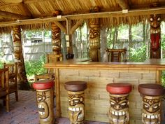 The carved wooden tiki bar stools really finish this outdoor tiki bar. Get me a blender stat!