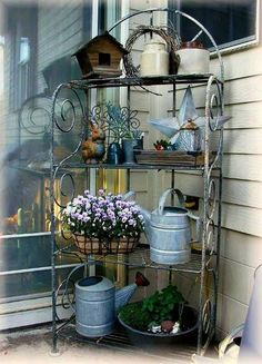 Designing a charming garden baker's rack. In her large garden shed, Jeanne Sammons kept a stash of rusty relics and flea market objects she rotated on her Baker's rack. Bakers Rack Decorating, Deck Decorating, Outdoor Spaces, Outdoor Living, Outdoor Decor, Outdoor Bakers Rack, Outdoor Shelves, Flea Market Gardening, Decks And Porches