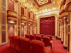 Palatial #home #theater in rich reds and golds, complete with a draped velvet curtain and faux box seats overhead. #hometheater