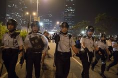 Umbrella Revolution Hong Kong, Police push back pro-democracy protesters who were trying to block a road outside the central government offices in the Admiralty district of Hong Kong on October 15, 2014. Hong Kong police vowed October 14 to tear down more street barricades manned by pro-democracy protesters, hours after hundreds of officers armed with chainsaws and boltcutters partially cleared two major roads occupied for a fortnight. AFP PHOTO / Ed Jones