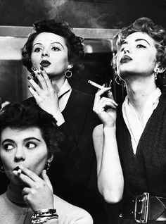 Models learning proper cigarette smoking technique in practice for TV ad. 1953 (via)