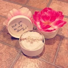 Flower girl proposals! -Paint a small round box with the color of your choice. -On paper doilies, write your message, cut to size and adhere it to the cap of the box.  -Cut the stem of a plastic flower and hot glue the blossom to the top I the cap.  -Fill box with a small piece of crumbled tissue paper and place your jewelry on top. - And your finished!