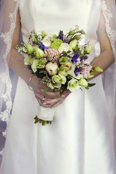Romantische zijde jurk met een kanten sluiter. In de handen van de bruid een prachtig boeket.