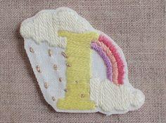 """白い木綿にアルファベットの""""I""""を手刺繍しました。図案は雨あがりの虹をデザイン。刺繍部分のこんもりすべっとした肌触りが、かくれた人気ポイン... ハンドメイド、手作り、手仕事品の通販・販売・購入ならCreema。"""