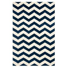 Showcasing chic chevrons in blue and ivory, this hand-tufted wool rug brings bold geometrics to your decor. Use it to define areas in the lounge or pair it w...