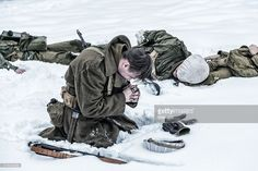 A single survivor WWII US Army soldier kneeling in the snow mourning and praying with rosary beads on a frozen winter battlefield surrounded by dead friends and comrades - ambushed combat infantry war casualties.