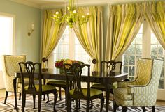 Love the smocked-top curtains--so unique.  Also love that the head chairs are upholstered.  Bold color choice for a dining room!