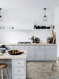 open kitchen without top cabinets. stone tile floor, white walls. colour blocking shelves.
