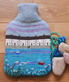 Knitted hot water bottle cover with seaside design, including bottle