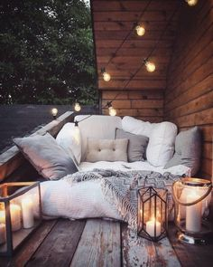 What a cozy spot for a warm summer night! It's everything that makes hygge what it is: the candles, cozy seating, lots of pillows, string lights, and a gorgeous location.
