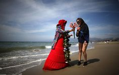 Spring de Haviland hands out carnations on the beach to celebrate the first day of spring in Santa Monica, California March 20, 2014. REUTERS/Lucy Nicholson