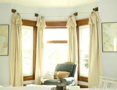 Drop cloth curtains hung on heavy twine and knobs. Great idea for my spare bedroom where its a world travelers theme. Love the maps on the wall near the window too!