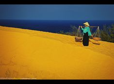 Vietnamese woman walking across the Red San Dunes called Mui Ne, Vietnam
