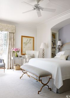 A gilded-metal bench from Joseph Konrad makes a striking statement in the master bedroom of a home in Maine designed by Suzanne Kasler.