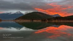 ice & fire by nojos8  clouds contrast forest lake light mountain mountains reflection sky snow sunrise travel trees water
