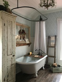 A shabby chic farmhouse bathroom with grey printed wallpaper, a white clawfoot tub, a shabby chic storage unit, a mirror in a wooden frame. Bad Inspiration, Bathroom Inspiration, Vintage Bathrooms, Vintage Bathroom Decor, Farmhouse Bathrooms, Country Bathrooms, Vintage Bathtub, Bohemian Bathroom, Chic Bathrooms
