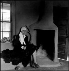 Georgia O'Keeffe by fireplace at home, Ghost Ranch, Abiquiu, New Mexico