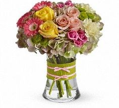 Fashionista Blooms Flowers are always in fashion! Especially this chic mix of pinks, greens and yellows, arranged in a style evoking the English hand-tied bouquet. It's a stylish surprise for any lucky lady.Mini pink gerberas, lush green hydrangea, yellow and pink roses, yellow carnations and green button mums are arranged in a clear concave vase that's trimmed with a chartreuse taffeta ribbon and pink raffia. #GiveFlowers