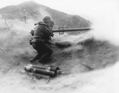 Powder smoke and dust billow as a recoilless rifle team of Co. D, 7th Infantry Regiment, 3rd U.S. Infantry Division, fire their weapon at Chinese Communist position on Hill 200 near Qnmong-Myon, Korea on November 9, 1951.