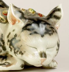 明治大正期の猫の九谷焼 Meiji/Taisho Period 1868-1926 This Kutani model of a tabby cat is decorated in various coloured enamels and gilt; the feline lies curled up and asleep, her front paw tucked under her chin.