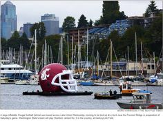 A large inflatable WSU Cougar Football helmet being towed across Lake Union.