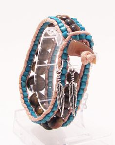 I made this bracelet with an interesting selection of choices. The outer rows are made with Turquoise dyed wood beads, while the center row is Tigers Eye gemstone beads that are graduated from 6mm to 14mm to give it a unique shape and look and it looks attractive on both sides. The bracelet is finished with a resin horn button and two silver tone feathers. All in all I think this piece has a Southwestern feel to it.  Fits a 7'' wrist comfortably.  $37.00